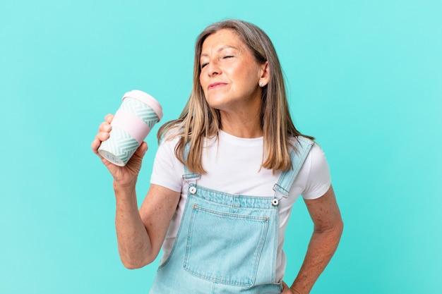 Hübsche frau mittleren alters, die einen kaffee zum mitnehmen hält