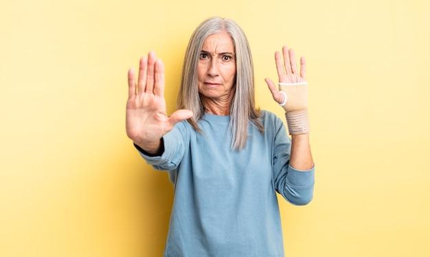 Hübsche frau mittleren alters, die ernst aussieht und offene handfläche zeigt, die stopp-geste macht. handverbandkonzept