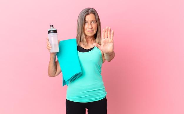 Hübsche frau mittleren alters, die ernst aussieht und offene handfläche zeigt, die stoppgeste macht. fitnesskonzept