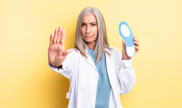Hübsche frau mittleren alters, die ernst aussieht und offene handfläche zeigt, die stoppgeste macht. fußpfleger-konzept