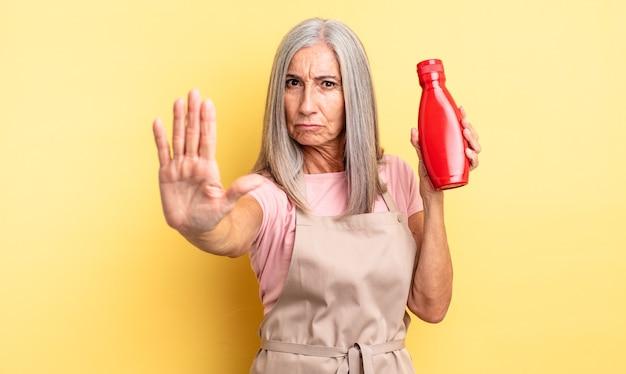Hübsche frau mittleren alters, die ernst aussieht und offene handfläche zeigt, die stoppgeste macht. ketchup-konzept