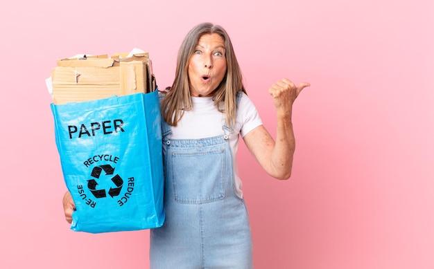 Hübsche frau mittleren alters, die erstaunt im unglauben beim recycling von kartonkonzepten aussieht
