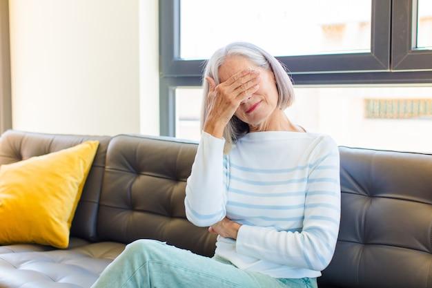 Hübsche frau mittleren alters, die gestresst, beschämt oder verärgert aussieht, kopfschmerzen hat und das gesicht mit der hand bedeckt