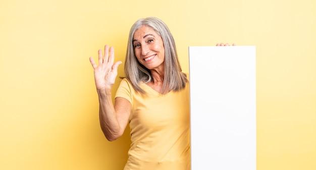 Hübsche frau mittleren alters, die glücklich lächelt, hand winkt, sie begrüßt und begrüßt. konzept der leeren leinwand