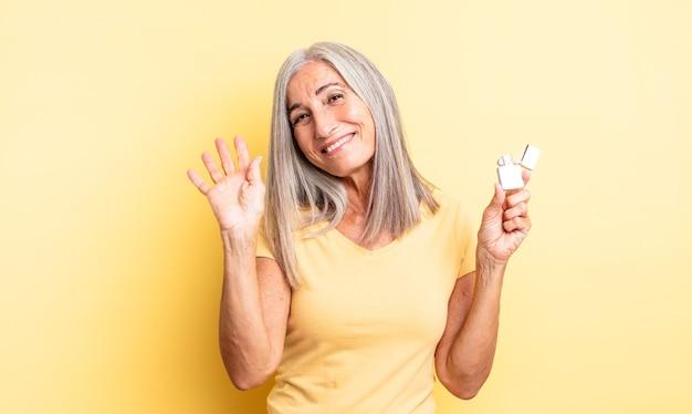 Hübsche frau mittleren alters, die glücklich lächelt, hand winkt, sie begrüßt und begrüßt. leichteres konzept