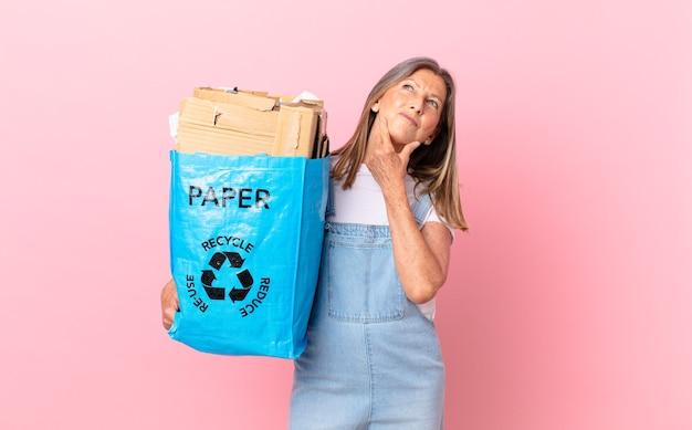 Hübsche frau mittleren alters, die glücklich lächelt und träumt oder an dem recycling-kartonkonzept zweifelt