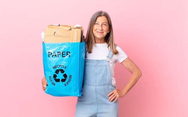 Hübsche frau mittleren alters, die glücklich mit einer hand auf hüfte und selbstbewusstem recycling-kartonkonzept lächelt