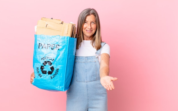 Hübsche frau mittleren alters, die glücklich mit freundlichem lächeln lächelt und ein konzept zum recycling von karton anbietet und zeigt