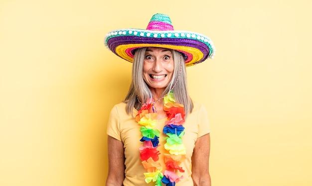 Hübsche frau mittleren alters, die glücklich und angenehm überrascht aussieht. mexikanisches partykonzept