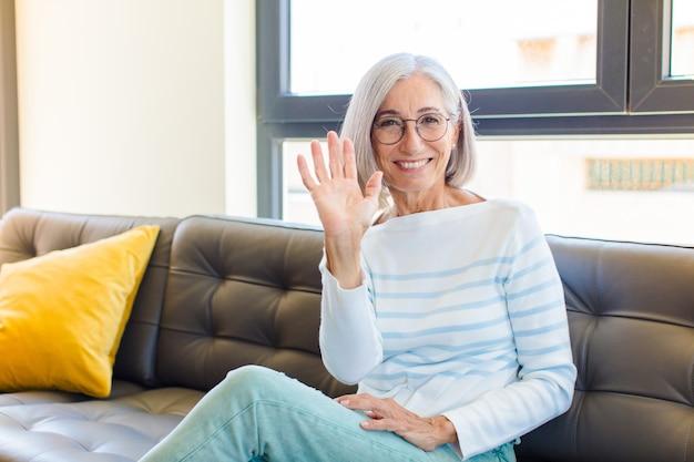 Hübsche frau mittleren alters, die glücklich und fröhlich lächelt, hand winkt, sie begrüßt und begrüßt oder sich verabschiedet