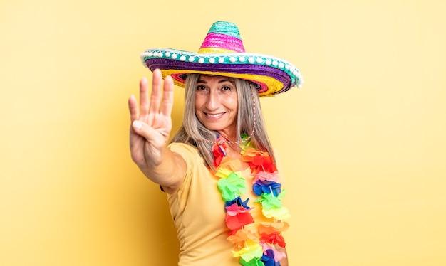 Hübsche frau mittleren alters, die lächelt und freundlich aussieht und nummer vier zeigt. mexikanisches partykonzept