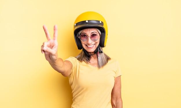 Hübsche frau mittleren alters, die lächelt und glücklich aussieht und sieg oder frieden gestikuliert. motorradhelmkonzept