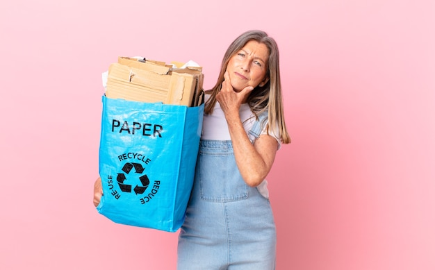 Hübsche frau mittleren alters, die mit einem glücklichen, selbstbewussten ausdruck mit der hand am kinn lächelt, recycling-kartonkonzept