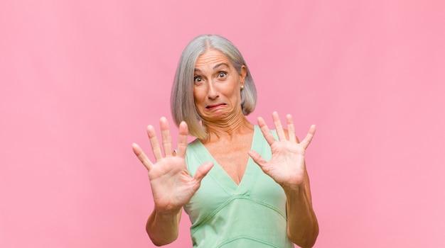 Hübsche frau mittleren alters, die mit einem verwirrten und fragenden blick auf sich selbst zeigt, schockiert und überrascht, ausgewählt zu werden
