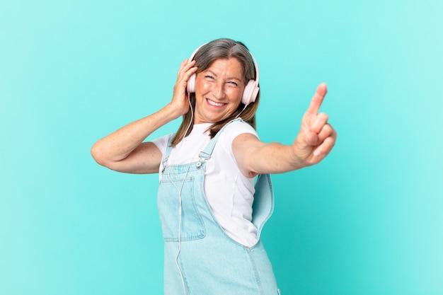 Hübsche frau mittleren alters, die musik mit kopfhörern hört