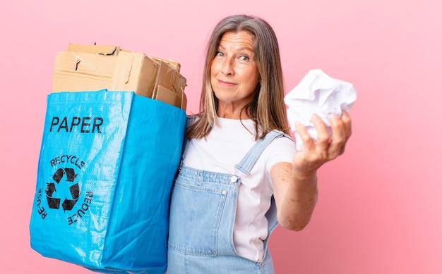 Hübsche frau mittleren alters, die papier recycelt