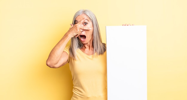 Hübsche frau mittleren alters, die schockiert, verängstigt oder verängstigt aussieht und das gesicht mit der hand bedeckt. konzept der leeren leinwand