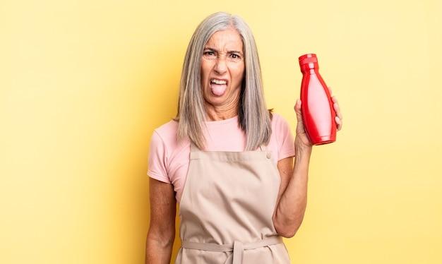Hübsche frau mittleren alters, die sich angewidert und gereizt fühlt und die zunge herausstreckt. ketchup-konzept