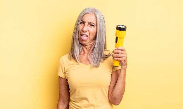 Hübsche frau mittleren alters, die sich angewidert und gereizt fühlt und die zunge herausstreckt. taschenlampenkonzept