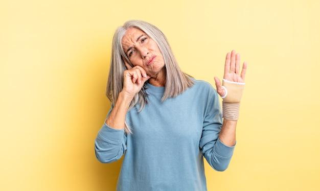 Hübsche frau mittleren alters, die sich gelangweilt, frustriert und schläfrig nach einer ermüdenden frau fühlt. handverbandkonzept