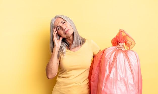 Hübsche frau mittleren alters, die sich gelangweilt, frustriert und schläfrig nach einer ermüdenden frau fühlt. müllbeutel aus plastik