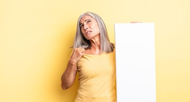 Hübsche frau mittleren alters, die sich gestresst, ängstlich, müde und frustriert fühlt. konzept der leeren leinwand