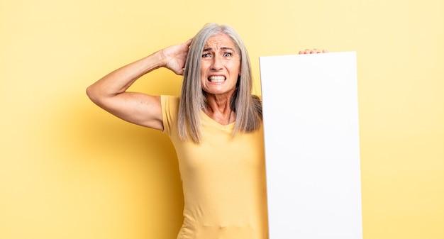 Hübsche frau mittleren alters, die sich gestresst, ängstlich oder ängstlich fühlt, mit den händen auf dem kopf. konzept der leeren leinwand