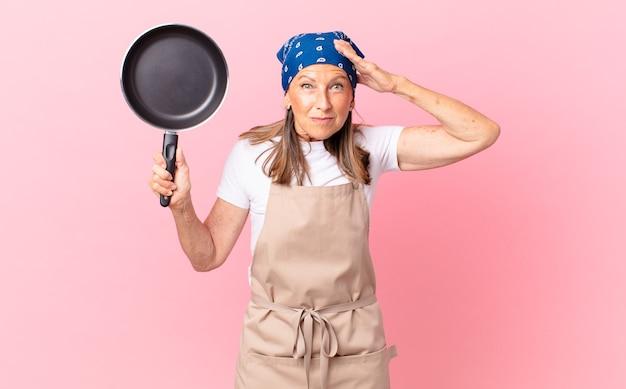 Hübsche frau mittleren alters, die sich gestresst, ängstlich oder ängstlich fühlt, mit den händen auf dem kopf und einer pfanne hält. kochkonzept