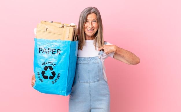 Hübsche frau mittleren alters, die sich glücklich fühlt und mit einem aufgeregten recycling-kartonkonzept auf sich selbst zeigt