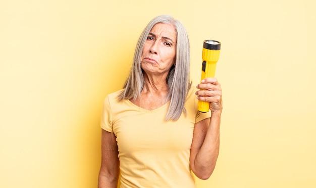 Hübsche frau mittleren alters, die sich traurig und weinerlich mit einem unglücklichen blick und weinen fühlt. taschenlampenkonzept