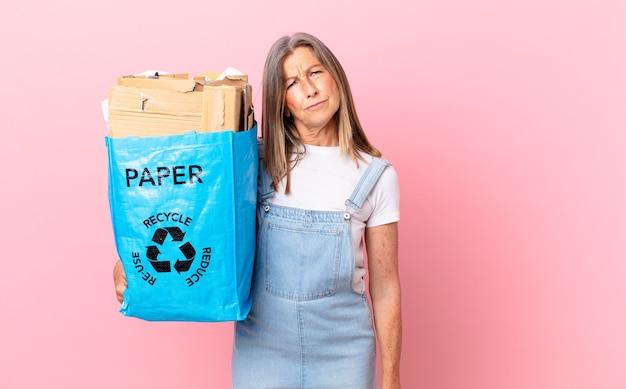 Hübsche frau mittleren alters, die sich traurig, verärgert oder wütend fühlt und zur seite schaut, recycling-karton-konzept