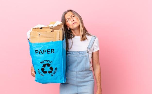 Hübsche frau mittleren alters, die sich verwirrt und verwirrt fühlt, recycling-kartonkonzept