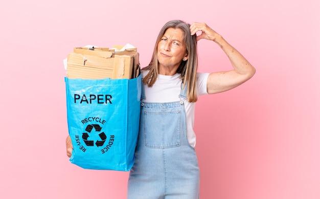 Hübsche frau mittleren alters, die sich verwirrt und verwirrt fühlt und sich den kopf kratzt, recycling-kartonkonzept
