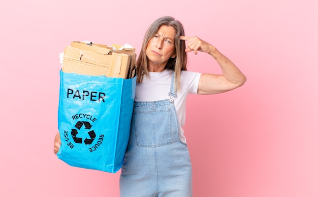 Hübsche frau mittleren alters, die sich verwirrt und verwirrt fühlt und zeigt, dass sie ein verrücktes recycling-karton-konzept sind