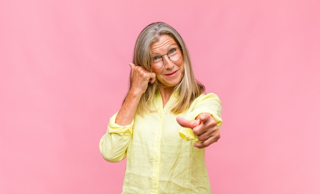 Hübsche frau mittleren alters, die sich verwirrt und verwirrt fühlt und zeigt, dass sie verrückt, verrückt oder verrückt sind