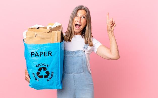 Hübsche frau mittleren alters, die sich wie ein glückliches und aufgeregtes genie fühlt, nachdem sie ein konzept zum recycling von karton verwirklicht hat