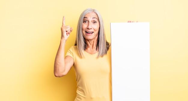 Hübsche frau mittleren alters, die sich wie ein glückliches und aufgeregtes genie fühlt, nachdem sie eine idee verwirklicht hat. konzept der leeren leinwand