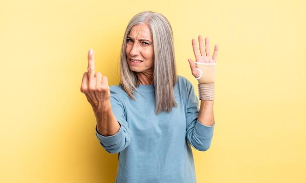 Hübsche frau mittleren alters, die sich wütend, verärgert, rebellisch und aggressiv fühlt. handverbandkonzept