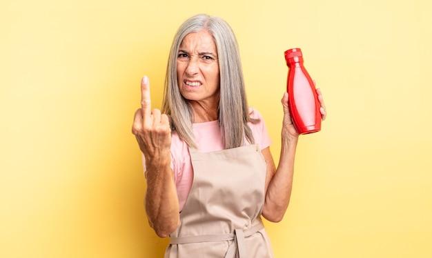 Hübsche frau mittleren alters, die sich wütend, verärgert, rebellisch und aggressiv fühlt. ketchup-konzept