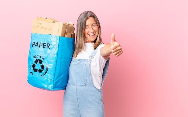 Hübsche frau mittleren alters, die stolz ist, positiv lächelt mit daumen hoch recycling-karton-konzept
