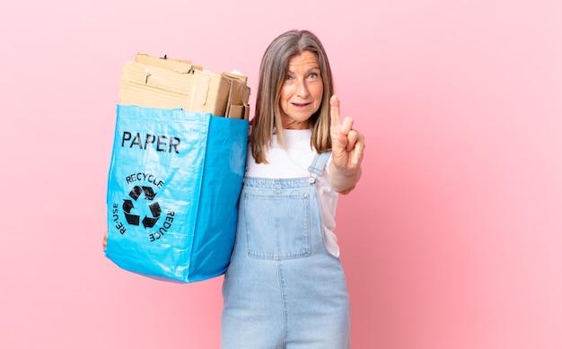 Hübsche frau mittleren alters, die stolz und selbstbewusst lächelt und das erste recycling-kartonkonzept macht