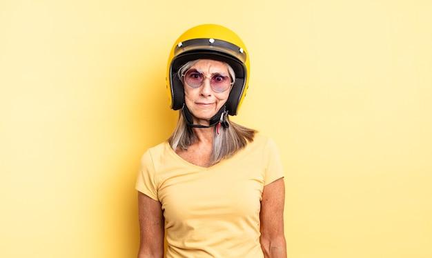 Hübsche frau mittleren alters, die traurig, verärgert oder wütend ist und zur seite schaut. motorradhelmkonzept