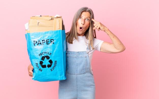 Hübsche frau mittleren alters, die überrascht aussieht und einen neuen gedanken, eine neue idee oder ein neues konzept für das recycling von karton verwirklicht