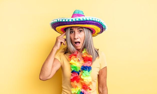 Hübsche frau mittleren alters, die überrascht aussieht und einen neuen gedanken, eine neue idee oder ein neues konzept realisiert. mexikanisches partykonzept