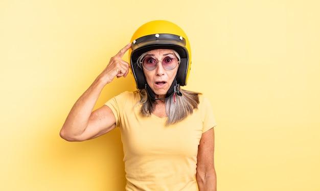 Hübsche frau mittleren alters, die überrascht aussieht und einen neuen gedanken, eine neue idee oder ein neues konzept realisiert. motorradhelmkonzept