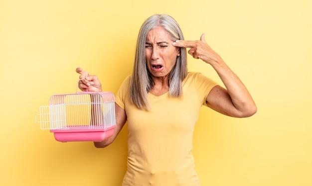 Hübsche frau mittleren alters, die unglücklich und gestresst aussieht, selbstmordgeste, die waffenzeichen macht. haustierkäfig oder gefängniskonzept