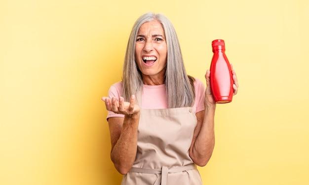 Hübsche frau mittleren alters, die verzweifelt, frustriert und gestresst aussieht. ketchup-konzept