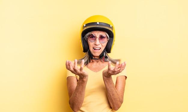 Hübsche frau mittleren alters, die verzweifelt, frustriert und gestresst aussieht. motorradhelmkonzept