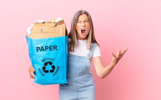 Hübsche frau mittleren alters, die wütend, verärgert und frustriert aussieht, recycling-kartonkonzept
