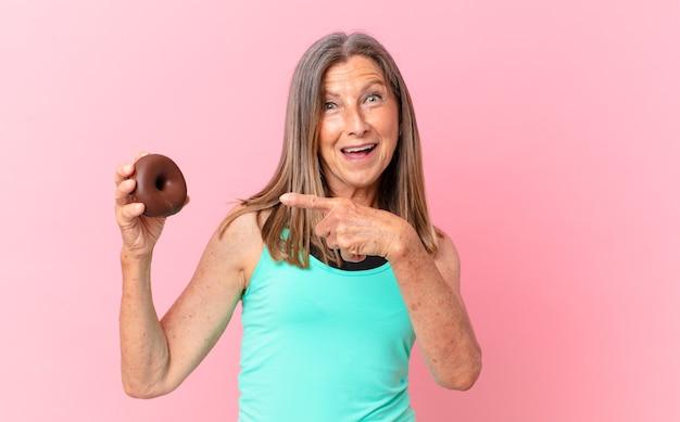 Hübsche frau mittleren alters mit einem donut